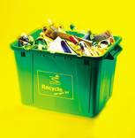 Full recycling bin with paper, card, glass, cans on yellow background